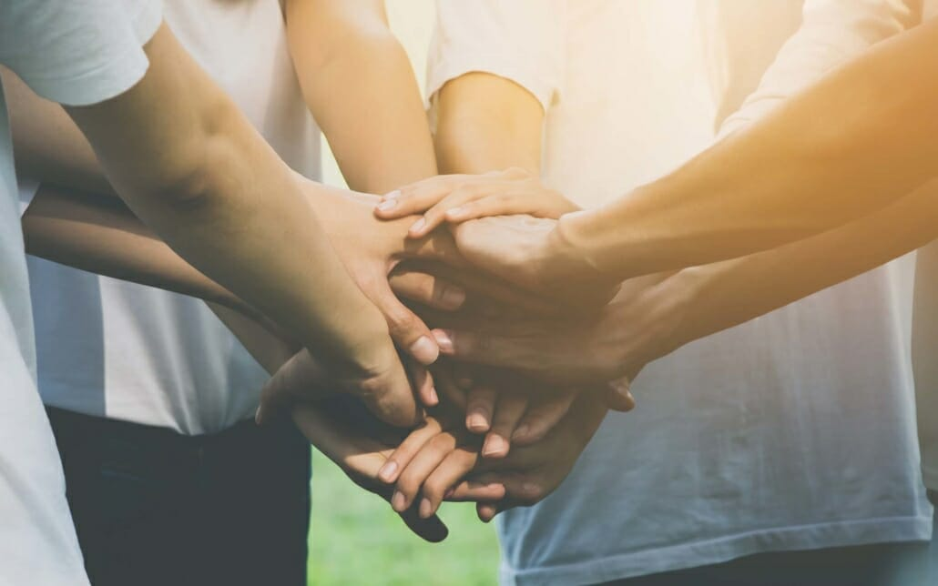 View of multiple people having hands in the middle